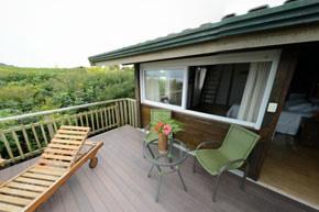 Duas acomodações localizadas no piso superior, cada uma com uma área de 19 m2 de área coberta. Possui uma cama de casal box Queen Size com massageador , sofá-cama de solteiro além de um mezanino com a :: Grajagan Surf Resort - Paranaguá PR