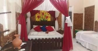 Apta adaptado para 4 pessoas, possui 1 cama casal  e 2 de solteiros, linda decoração de cama indiana com véu vermelho. :: Pousada Praia dos Milagres - Olinda PE
