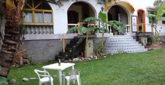 Jardim - estacionamento interno em 1Ao. plano. Em 2o plano a fachada da casa c/ entradas dos Flats 2 e 3 além da entrada da Recepção.  :: Itaipu Flats Pousada - Niterói RJ